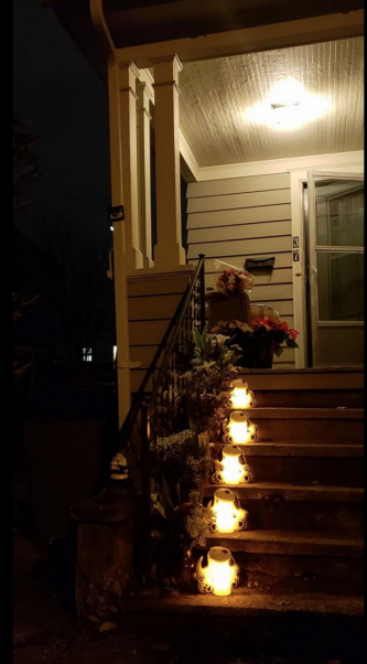 Flowers lanterns on steps of house where five dogs died